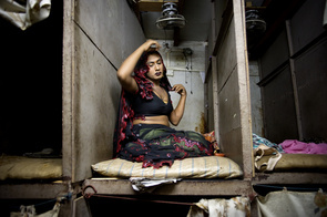 A male transsexual prostitute selling sex inside a brothel in Mumbai's infamous red light district Kamathipura.  These sex workers service between 20 to 50 customers a day and earn on average 1-2 US Dollars per customer with half going to the brothel owner. The Indian government provides free condoms to brothels, but despite this fact, approximately 50% of the sex workers are HIV positive. Critics and NGO workers claim that the Indian government is hiding the fact that the country is facing an epidemic, and nobody really knows how many people are infected with the virus.