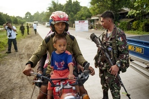 A Muslim man and his son are stopped by military personnel at a roadblock in the vicinity of MILF (Moro Islamic Liberation Front) territory on the second largest and southernmost island of the Philippines.  The war in Mindanao is finally over after the government and MILF (Moro Islamic Liberation Front) guerrillas have finally signed a peace settlement. The newly created autonomous Muslim region of Bangsamoro is about to be drawn on the map.