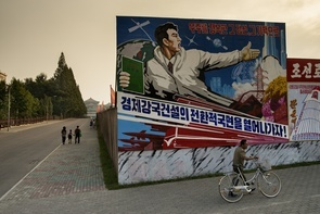 """Rather than advertising billboards, North Korea's streets are filled with combat propaganda with texts expressing that """"with determination and the right spirit, we can conquer the universe, let's get on with the transition phase to build an economic superpower!"""".  60 years after the Korean War, it is clear that not much has changed in North Korea. The country still remains under heavy censorship, with only a small portion of the population living the life of what we call """"middle class"""". The people of North Korea are forced into believing that working for the greater good of the state is the formal way of presenting their national determination. The city of Pyongyang is outdated, with only a handful of cars driven by those who are a bit more fortunate. Propaganda rates are high, with many billboards displaying missiles and world domination regimes. North Korea remains a strictly isolated country where people do not have the privileges that we take for granted."""