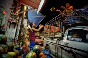 A Burmese man and woman help each other unload watermelons from a truck at the fruit market in Phuket; they only make up for two of the 1.23 million undocumented migrant workers in Thailand.  Recently, there has been an increasing number of Burmese immigrants moving to Thailand in the hopes of getting better employment. It is estimated that more than two million Burmese people live in Thailand, of which 300,000 live in Phuket. It is unknown how many illegal immigrants there are, however relations between Myanmar and Thailand has strengthened recently, which makes it easier for a Burmese immigrant to acquire a work permit. On the other hand, problems that the Burmese immigrants face include heavy costs on work permits and complicated systems that put many of the immigrants in the hands of agents and human traffickers leaving the immigrant in skyrocketing debt.
