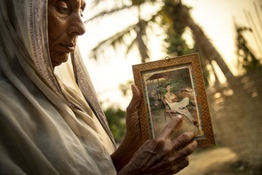"""Manda Devi Mishra shows a framed photograph of her son who lost his life to the dangerous working environments of Qatar.  Oil money and migrant workers are exactly what is required to build the infrastructure and stadiums of Qatar as they plan to host the World Cup in 2022. The migrant workers who travel to the Persian Gulf hope to find better jobs and a future for themselves, however, the common case is that they end up working in slave-like conditions on dangerous workplaces – Amnesty wrote in a report. After having the highest GDP per capita, Qatar is going to invest a staggering 775 billion on the stadiums that will hold the World Cup in 2022. This has led to an influx of migrant workers moving to the middle-east for jobs. Nepal alone delivers 1500 people a day to work in the Gulf with the main spot of attention being Qatar.  There are more than half a million migrant workers in Qatar performing practical work on construction sites with Nepalese people being the largest group as their wage demands are generally lower. Words of high wages and good conditions are often untrue leaving many workers stuck in the middle-east against their will. Many others return home with a large debt - others don't return home at all. """"He was only 35 years old"""" says Manda Devi Mishra as she buries her face in the palms of her hands. Manda Devi Mishra was notified 10 months after an accident had killed her son Subodha Mishra in his Qatari workplace. Details are still unclear as the employer will not communicate directly with the family. What she has been told is that an accident involving a track backing into him was the cause of death. Manda comes from a village called Bhramapura, a sleepy farming town in the southeastern parts of Nepal. Located in the in the lowlands close to the Indian border, it is one of the poorest places in Nepal. Many migrant workers originate from these locations but what makes Bhramapura special are the brick walls and higher literacy rates than its neighbo"""