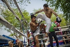 A foreign challenger lands a flying knee kick to the face of a convict during a boxing match at a Khlong Pai prison; these prison fights allow the opportunity for convicts to reduce their sentences by winning their matches.   Thai prisoners, many of them hardened by years of incarceration, were pitted against free foreign fighters in both Muay Thai and traditional boxing bouts. Both sides were competing for a little cash, but the Thai prisoners were also fighting for their lives, literally. Prisoners who win a championship and thereby bring glory to the prison have a realistic shot at having their sentences commuted. The organizer said this goes for any prisoner regardless of the magnitude of their crime, but he was also quick to point out that prisoners are judged from a holistic perspective that incorporates their behavior outside of the ring. That said, it doesn't diminish the gravity of what's at stake. - Coconuts Bangkok