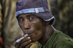 A Myanmar day laborer smokes a homemade cigarette during a break from carrying  40 plus kilogram baskets of river gravel.  Each worker is paid around 4 cents per basket.  Demand for construction supplies has increased as Myanmar opens to the world.