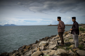 A father and his son look out over the sea at the Banda Aceh coastline. It was here that the giant tsunami in 2004 withdrew.   The tsunami of December 2004 was as deadly as the atomic bombs that were dropped on Hiroshima and Nagasaki together; but at the same time paved the way for peace in Indonesia. Inspired by Swedish social democracy, Aceh is now trying to build a functional society over the rubble left by the tsunami, however, the trauma left by the wave can still be seen 10 years later in many aspects of life. Many of those who survived the devastation were given compensation in the form of houses and aid from international organisations. However, there are still some families left in the former IDP refugee camps who have settled in permanently due to the promising of aid that never came. The tsunami did however, indirectly bring about peace and a new government as it ended the movement that started in 1976 to free Aceh, called the GAM rebellion against the central government in Jakarta. In the peace negotiations that followed the tsunami, Aceh was given regional autonomy, the first region in Indonesian allowed to set up local political parties and impose local laws. It remains forbidden to hoist GAM's former flag. Aceh is also believed to be one of the first regions in Indonesia to convert to Islam and have also introduced Sharia law and corporal punishment for multiple offenses.