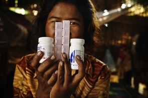 Phhoung, 36, displays medicine in her home. A few months ago she could not afford medecine to treat HIV/AIDS, she wighted 20 kilos less and was unable to work or take care of her baby. After getting help from NGO workers, she recovered and regained her lost weight.
