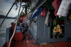 """Illegal migrant workers on a fishing boat in Phuket, Thailand.  Every year hundreds of thousands of tourists come to Thailand. But in the shadow of mass tourism, there is a different reality. Reporters have found serious grievances among migrant workers in hotels used by the tourists. Trafficking and modern slavery are part of everyday life for those who pay the highest price to be smuggled into the country.   Htoo Aung says that seven other Burmese and he were led by smugglers through the jungle for eight days. They slept in the open air for short periods during the day. Under the cover of darkness, they took a long detour into the thorny terrain to bypass roadblocks controlled by the Tatmadaw, the Burmese junta's feared military force. From Htoo Aungs small village in the state of Mon in one of the world's least developed countries, the group slowly moved southwards.   """"I was terrified. We were passed by a soldier patrol just meters from the bushes where we were hiding. But they did not see us."""" Says Htoo Aung  Many of the migrant workers who came over from Myanmar have made it to Thailand illegally. They saw little chance in Burma for a life of proper employment and so many of them made the choice to contact a broker that could help them get across the border illegally to come and work in Thailand as hotel staff or fishermen. Most of these workers had to risk their lives being smuggled through thick terrains of jungle and once they got to Thailand, they were instantly in debt as most don't have enough to pay the brokers for the smuggle.   According to a report by the International Labor Organization, migrant workers generate up to the equivalent of almost $15 million per year to the Thai economy. But these figures were recorded in 2007; since then the estimated number of migrant workers in the country has doubled - from 1.8 million to almost 4."""