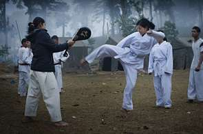 A female soldier of the People's Liberation Army (PLA) swings her leg during the martial arts training in the camp.