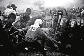 First Place - Lino G. Escandor II: Anti-riot policemen in the Philippines stand their ground as rioters make their way into a barricade despite a water canon's assault.