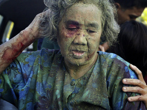 A woman is helped to a local hospital after suffering injuries in a bomb blast at a morning market in southern Thailand's Yala province April 12, 2007. Eleven were injured by the blast, which was triggered by militants, police said.