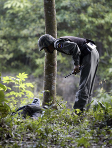 A Thai soldier looks over the body of a suspected militant in Thailand's Yala province, nearly 1084 km ( 672 miles) south of Bangkok on May 29, 2008. Four militants were killed after an encounter with a soldier, police said.
