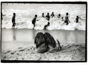 First Place - Tawatchai Pattanaporn: A pair of Muslim women on a beach watching a group of quintessentially Thai children playing in the surf. The photograph illustrates the huge cultural divide that exists in sourthern Thailand, and how Thailand's predominantly Buddhist culture is often at odds with Muslim social rules.