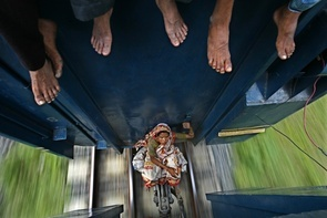 A woman sits between carriages as a train travels to Mymensing from Dhaka in Bangladesh. Millions of residents travel from the capital city to celebrate the Muslim Eid al-Fitr holiday, and many cannot afford the ticket price.