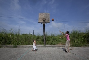 Single mom Abegail plays basketball with her son who has Down Syndrome disease, early in the morning after long hours of working in the red light district as a bar girl. This basketball court near their backyard serves as a safe playground for her kids.  (Photo By Jae-hyun Seok)