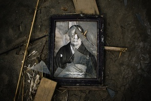 A broken picture frame lies in the mud within the exclusion zone, about 12 miles (20 kilometers) away from Fukushima Nuclear Power Planton April 7, 2011 in Minamisoma, Fukushima Prefecture, Japan. The 9.0 magnitude strong earthquake struck offshore on March 11 at 2:46pm local time, triggering a tsunami wave of up to ten metres which engulfed large parts of north-eastern Japan, and also damaging the Fukushima nuclear plant and threatening a nuclear catastrophe. The death toll continues to rise with numbers of dead and missing exceeding 20,000 in a tragedy not seen since World War II in Japan. (Photo by Athit Perawongmetha/Getty Images)