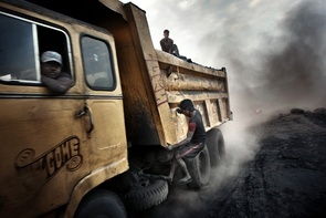A standard assault of the coal truck: these teenagers jump onto the moving trucks, risking their life to steal a few lumps of coal for the black market. Jharkhand: a mining state of Eastern India – it is the mined coal from here that has made this Indian state world-known for being the second largest coal producer. Second only to China, India extracts from it's soil a quantity of coal overly sufficient for its energy and transport needs; the remainder is exported worldwide.  90% of the mines, which work continuously, are open-air and most of these work upon auto-combustion which releases an incalculable amount of carbon monoxide – the  cause of global warming. Whole forests have been destroyed to make way for this brutal extraction and to satisfy the country's ever-growing development. The concessions for coal mining are granted by the central government and managed by both state and private owned enterprises, thus creating a social and economic imbalance in the area.  Everything rotates around the mining industry which was once an agricultural area and is now fully converted to coal mining.  Many people are jobless and can not cultivate their fields because groundwater aquifers are polluted by agents deriving from coal combustion. These thousands of people, without economic opportunities, are forced to work illegally, in nonexistent safety conditions and with state police always on their backs. The dramatic increase of pollution due to this brutal coal extraction is causing the population to suffer from the most serious respiratory diseases, from lung cancer to silicosis, from many typologies of tuberculosis to obstruction of the respiratory system.  Related, as well, are severe blood diseases caused by carbon monoxide inhalation, cardiac disfunction  and a short-life expectancy (which does not exceed the 50 year mark). These diseases are destroying the future of this Indian state in the name of progress. Photo by Erik Messori