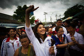 Yingluck Shinawatra raises her arm with a trademark salute, making the #1 sign of her party because they are first on the ballot sheet during a final campaign rally on July 2, 2011 in Bangkok, Thailand. Thailands voting polls open on July 3, with red shirt movement supported Yingluck Shinawatra, younger sister of fugitive and former prime minister Thaksin Shinawatra who was ousted in 2006, running against Prime Minister Abhisit Vejjajiva's Democrats. This will be Thailand's fourth election in seven years. (Photo by Athit Perawongmetha/Getty Images)