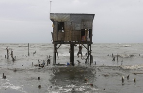 A man hangs on to what remains of a house that was built on stilts as he tries to recover belongings after a powerful Typhoon Nesat wiped out most of their neighbors' homes along a coastal village in Navotas, north of Manila, Philippines on Wednesday Sept. 28, 2011. Emergency services and residents in the Philippine capital cleaned up and restored electricity Wednesday after the powerful typhoon unleashed floodwaters and fierce wind that killed at least 20 people and sent huge waves crashing over seawalls. (AP Photo/Aaron Favila)
