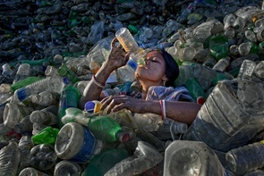 A day labourer takes a drink from a bottle while working in a small plastic recycling factory in Sylhet for survival. Her job is to separate the different coloured bottles, then washing and dry them for a daily wage of about 100 to 120 taka (US $1.25 to US $1.50). She will collect any left over cooking oil to take home for her family. Nearly 60% of all villagers in Bangladesh live below the poverty level, and many come to the cities to find work.