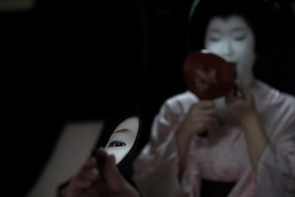 This is the day when Ichiraku, 20, becomes a Geiko from a Maiko. She looks in a hand mirror to paint her lips.