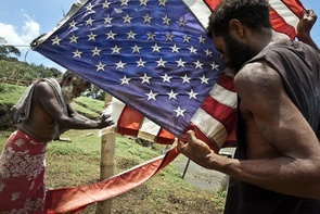 "Followers of John Frum Cargo cult during the everyday ceremony of American flag raising. For them an American flag is a symbol of ""cargo"" (coca-cola, canned fish and meat and other benefits of Western civilization). Lamakara village, Tanna island, Vanuatu."