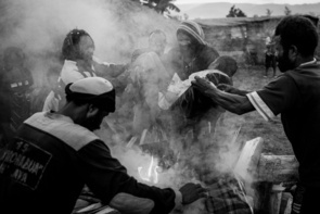 """Dewi's lifeless body is carried into the fire by her uncle to be cremated.Dewi (20) is a young wife who died from AIDS after contracting HIV from her husband.  Dewi kept her status a secret from her family.  Before her death, Dewi's family used a traditional healing method of cutting her body to let """"dirty"""" blood out in order to cure her illness.  Outside, men cut wood into small pieces and stacked them to prepare for her cremation.  A local NGO called Caring Hands donated money for cremation, since Dewi's family was too poor to have her buried.  A pastor led the ceremony and prayed before Dewi's body was place on top of the funeral pyre.  It is common for husbands to keep their status from their wives or vice versa due to shame and fear of discrimination or punishment.  Even after testing positive for HIV, many still disregard using condoms to avoid drawing suspicion.  As a result, HIV is often passed on to their spouse."""