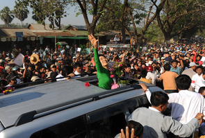 Myanmar opposition leader Aung San Suu Kyi (C) waves as she crosses a crowd of supporters while arriving for a political rally as part of her electoral campaign at a stadium in Pathein, some 200 kms west of Yangon on February 7, 2012.