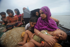Rohingya Muslims, trying to cross the Naf river into Bangladesh to escape sectarian violence in Myanmar, look on from an intercepted boat in Teknaf on June 13, 2012.At least 50 people have died in western Myanmar's Rakhine state in more than a week of sectarian violence and revenge attacks between Buddhists and Muslim Rohingya.