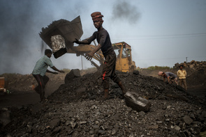 En last bil lastar av sten blandat med kol i från gruvorna som arbetare sorterar för hand i en av kolgruvorna i Jharia. Laborers are digging up coal using excavators at the Jharia coal mine.  Jharia in India's eastern Jharkand state is literally in flames. This is due to the open cast coal mining that takes place in the area. For more than 90 years, the Jharian coal mines have been alight with coal mining villages of around seven hundred thousand people settling in. Most of the mining is done with open cast as the price to mine is relatively lower to produce the profits. However, open cast mining does have its disadvantages including the release of toxic chemicals into our atmosphere.   Everywhere you look, there will be coal to mine. And so villagers in Jharia often go out with their own shovels to mine whatever coal there is in the ground to support their families after selling the coal at the market center. The open pits of coal on the other hand, often catch fire due to careless cigarette bud tipping or due to lightning strikes in the area and will burn for years to come; spewing toxic and hazardous chemicals into the Earth's atmosphere. About 1.4 billion tonnes of carbon dioxide gets pumped into the atmosphere  and could even be considered as the 4th most polluting area of India. Life however, is something that most will fight for, and if destroying the environment means feeding their families; workers will continue to run outside with their shovels and dig up all the coal they can find to survive.