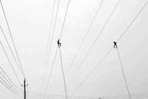 Electricians are working on a wire above the ground without any safety measures in Dhaka, Bangladesh on 14 May 2014. All linemen, especially those who deal with live electrical apparatus should use personal protective equipment as protection against inadvertent contact. Most of the times in Bangladesh electricians work without any safety measures like rubber gloves, rubber sleeves, bucket liners and protective blankets etc. According to the Bangladesh Institute of Labour Studies (BILS), 7,199 workers were killed and 17,138 were injured in workplace accident and violence in the last 10 years. Between January and December 2013, at least 1,912 workers were killed and 5,738 were injured.