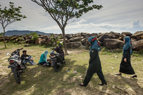 During a patrol on the northern coastline of Banda Aceh, the Sharia Police (Wilayatul Hisbah) find one boy and two girls hanging out together. They then proceed to lecture them on how the two different genders should not mix with each other in this way. The Sharia Police take down their personal details and give them their first warning out of three; those who receive three will be sent to a religious rehabilitation centre.   In the autonomous region of Aceh, there are two types of police forces: the standard police, who persecute and investigate everything from everyday crimes to murder; and the Sharia police or Wilayatul Hisbah, who are in charge of tracking people for human sins against the Islamic religion. The punishments range from religious rehabilitation to lashings.  After a Sharia patrol car arrived at a scene of a girl gang, the girls immediately started screaming and dissipated as the grim faced officials dismounted the green military people carrier. Only 20 year old Desi remained behind as she worked in a shop nearby. She was given a verbal warning; she was inappropriately dressed although what she claimed was that the weather was too hot around there and she only wore short sleeves to stay cool whilst she worked.   Among the criminal offenses and wrongdoings are alcohol, gambling, homosexuality, extramarital sex and khalwat (affectionate contact between unmarried couples). The latter, along with disobedience to the clothing rules, are what the Sharia Police or Wilayatul Hisbah usually prosecute people for.