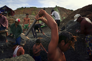 A team of miners work in a jade mine. Some miners work alone while some like this young men here work by a team in a small plot land that is owned by thier 'Lao-ban'. July 2014, Hpakant, Myanmar.