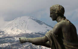 The top of vesuvius Volcano covered by snow is seen from the archaeological area where are the ruins of Pompeii, the ancient Roman town buried by the eruption of Vesuvious on August 25 of 79AD. A cold wave has hit the italy with snowfalls and low temperatures.