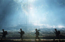 Humanitarian commandos, Karen State - Karen guerillas in charge of protecting their mobile medical team are walking through a rice field.
