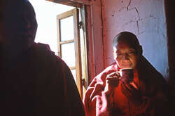 Tashi, a nun from the Sin Sur monastery, and the guru of the young nun Yanghin, drinks butter tea at the Tawang monastery.