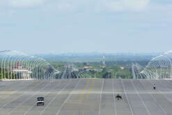 A man carrying a bundle of grass crosses a 20-lane Naypyidaw avenue.