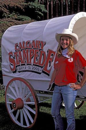 Canada, Alberta, Calgary, Calgary Stampede, Girl Posing In Front Of Wagon.