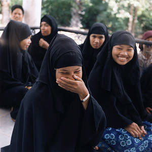 Sophiyas Binti Abdullah, 17, laughs at having her picture taken with other girls, as they wait to start their Islamic instruction at the Masjid al Husainiah in Kagu Jury Village.