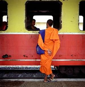 A Buddhist monk chats with a fellow passenger as they wait for the start of the 14-hour train ride through the countryside between Phnom Penh and Battambang.  