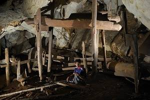 Local villager Thi Moo sits beneath an ancient teak burial coffin in Bo Khrai cave in Mae Hong Son Province, Thailand. The remnants of several other coffins, dilapidated by time, lie scattered about. Approximately 1,700 years ago, people dragged dozens of these massive coffins and pillars deep into this cave for what were likely secondary burials. Centuries of isolation have kept this and more than 80 other cave coffin burial sites in relatively good condition. A lack of funding keeps them relatively unstudied.